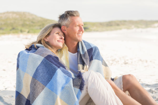 A couple under a blanket at the beach feeling confident about their smiles with All-on-4.