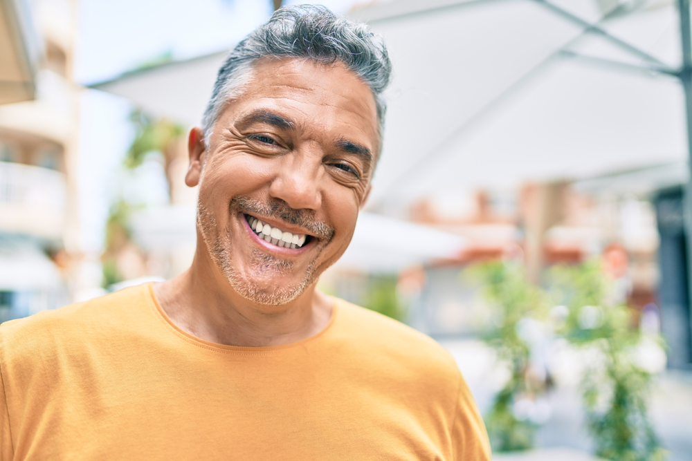 An older man smiles outside after finishing his dental implant process.